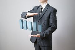 Businessman presenting a successful sustainable development. Business concept. Businessman presenting a successful sustainable development on a bar chart on gray Stock Photos