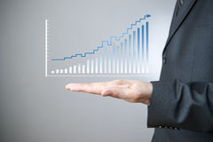Businessman presenting a successful sustainable development. Business concept. Businessman presenting a successful sustainable development on a bar chart on gray royalty free stock photo