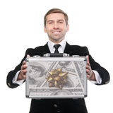 Businessman presenting a suitcase full of one hundred US dollars Stock Photos
