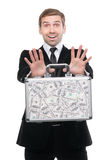 Businessman presenting a suitcase full of one hundred US dollars Royalty Free Stock Images