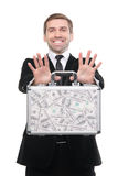 Businessman presenting a suitcase full of one hundred US dollars Stock Photo