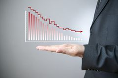 Businessman presenting a sustainable decrease development. Business concept. Businessman presenting a sustainable decrease development on a bar chart on gray Stock Images