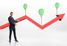 Businessman presents growing red arrow with air balloons. Stock Image