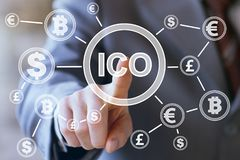 Businessman presses currencies button ICO Initial Coin Offering on a virtual digital electronic user interface.