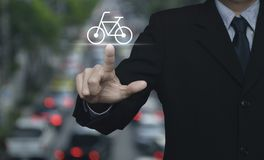 Business service bike concept. Businessman pressing bicycle flat icon over blur of rush hour with cars and road, Business service bike concept Royalty Free Stock Photo