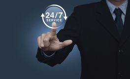 Businessman pressing button 24 hours service icon on blue backgr Stock Photo