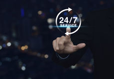 Businessman pressing button 24 hours service icon over blur ligh. T city tower background, Full time service concept Royalty Free Stock Image