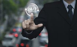 Full time service concept. Businessman pressing button 24 hours service icon over blur of rush hour with cars and road, Full time service concept Royalty Free Stock Images