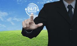 Full time service concept. Businessman pressing button 24 hours service icon over green grass field with blue sky, Full time service concept Royalty Free Stock Image