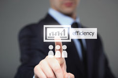 Businessman pressing button on touch screen interface and select Efficiency. Royalty Free Stock Images