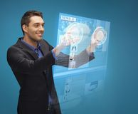 Businessman pressing buttons on virtual screen Stock Photo