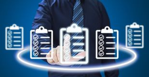 Businessman pressing check list icon over blue background. Check list concept stock photography