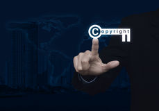Businessman pressing copyright key icon over map and city tower Stock Photos