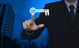 Copyright and patents concept. Businessman pressing copyright key icon over modern office city tower, Copyright and patents concept Stock Image