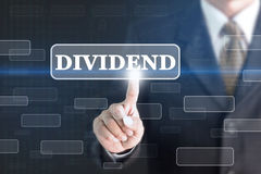 Businessman pressing DIVIDEND concept button. Can be used in advertising Stock Images
