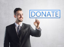 Businessman pressing a donate sign Stock Photo