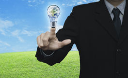 Businessman pressing earth globe in light bulb over green grass Stock Images