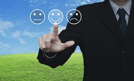 Business customer service evaluation and feedback rating concept. Businessman pressing excellent smiley face rating icon over green grass field with blue sky Stock Image