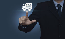 Businessman pressing free delivery truck icon on blue background Royalty Free Stock Photos