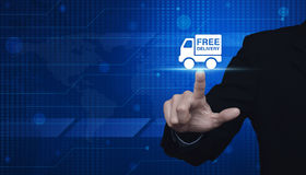Businessman pressing free delivery truck icon over digital world Stock Image