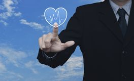 Business medical health care service concept. Businessman pressing heart beat pulse flat icon over blue sky with white clouds, Business medical health care royalty free stock photos