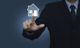 Businessman pressing house icon on blue background, Real estate Royalty Free Stock Image