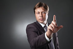 Businessman pressing an imaginary button on bokeh Stock Photo