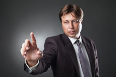 Businessman pressing an imaginary button on bokeh Royalty Free Stock Photography