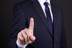 Businessman pressing an imaginary button on over dark background Stock Photography