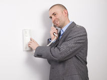Businessman pressing an intercom Stock Images