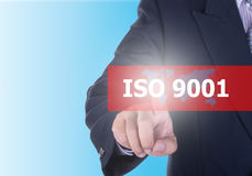 Businessman pressing iso 9001. Button on virtual screens with word ISO 9001 blue background. Quality standart iso concept Royalty Free Stock Image