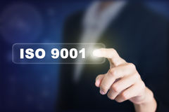 Businessman pressing a ISO 9001 concept button. Stock Image