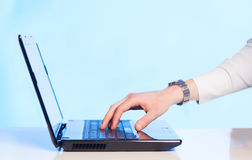 Businessman pressing modern laptop computer on colorful backgrou Royalty Free Stock Image