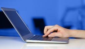 Businessman pressing modern laptop computer on colorful backgrou Stock Photos