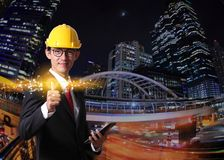 Businessman pressing modern social buttons on a night light city. Background. Businessman engineer pressing virtual button online.Engineering engineer Royalty Free Stock Images