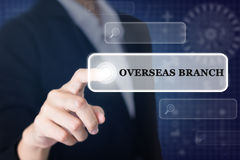 Businessman pressing a OVERSEAS BRANCH concept button. Stock Images