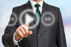 Businessman pressing play button on a virtual background Stock Image