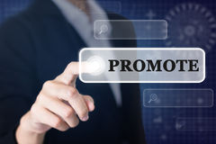 Businessman pressing a PROMOTE concept button. Can be used in advertising stock photos