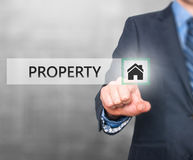 Businessman pressing property button on virtual screens Stock Photos