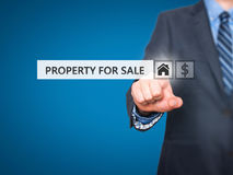Businessman pressing property for sale button on virtual screen Stock Photography