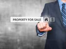 Businessman pressing property for sale button on virtual screen Royalty Free Stock Photos
