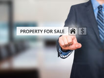 Businessman pressing property for sale button on virtual screen Stock Images