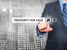 Businessman pressing property for sale button on virtual screens Royalty Free Stock Photography