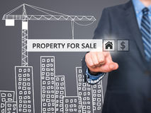 Businessman pressing property for sale button on virtual screens Stock Photo
