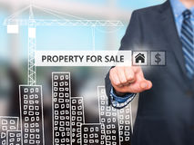 Businessman pressing property for sale button on virtual screens Royalty Free Stock Image