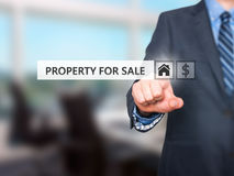 Businessman pressing property for sale button on virtual screens Royalty Free Stock Images