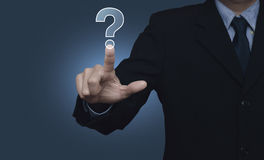 Businessman pressing question mark sign icon over blue backgroun Stock Images
