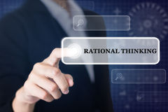 Businessman pressing a RATIONAL THINKING concept button. Stock Image