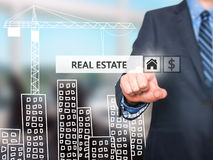 Businessman pressing real estate button on virtual screens Royalty Free Stock Photo