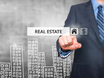 Businessman pressing real estate button on virtual screens stock photography